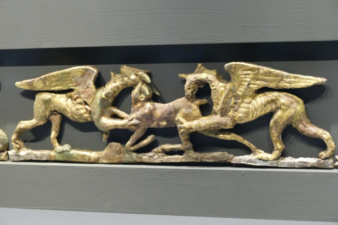 Gilded cay tablets depicting griffens attacking a deer from a burial couch. Pella Museum